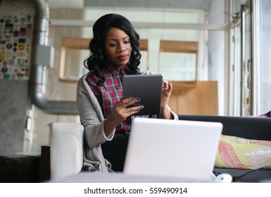 African American woman typing on her tablet.