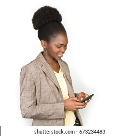 African American woman using a cell phone on a light grey background wearing a blazer with room for copy