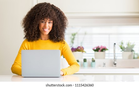 African american woman using computer laptop at kitchen with a happy face standing and smiling with a confident smile showing teeth