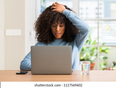 African american woman using laptop computer at home stressed with hand on head, shocked with shame and surprise face, angry and frustrated. Fear and upset for mistake.