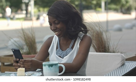 African american woman using phone, while sitting in outside cafe