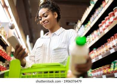 African american woman using phone shopping groceries buying food and browsing discounts and coupons standing with cart in supermarket. Female customer buys groceries in shop. Buyer's application