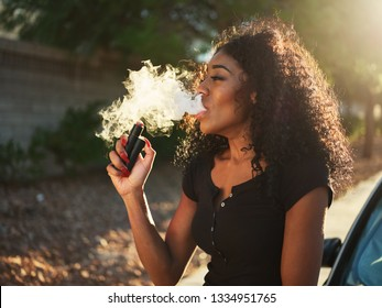 african american woman vaping and exhaling cloud of smoke