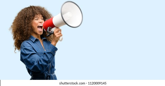 African american woman wearing blue jumpsuit communicates shouting loud holding a megaphone, expressing success and positive concept, idea for marketing or sales