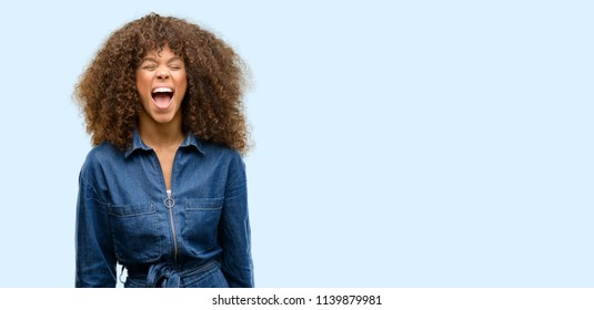 African american woman wearing blue jumpsuit stressful, terrified in panic, shouting exasperated and frustrated. Unpleasant gesture. Annoying work drives me crazy