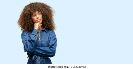African american woman wearing blue jumpsuit thinking and looking up expressing doubt and wonder