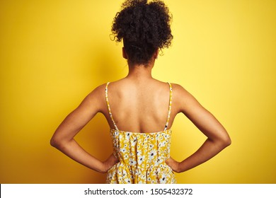 African american woman wearing casual floral dress standing over isolated yellow background standing backwards looking away with arms on body