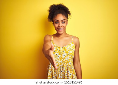 African american woman wearing casual floral dress standing over isolated yellow background smiling friendly offering handshake as greeting and welcoming. Successful business.