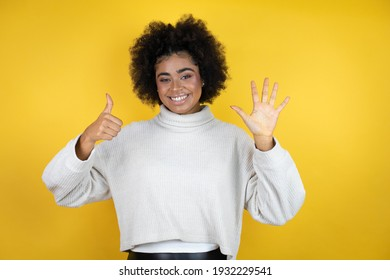 African american woman wearing casual sweater over yellow background showing and pointing up with fingers number six while smiling confident and happy