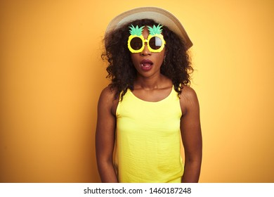 African american woman wearing funny pineapple sunglasses over isolated yellow background afraid and shocked with surprise expression, fear and excited face.