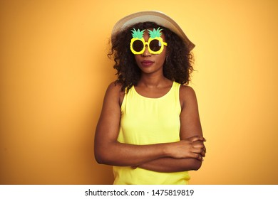 African american woman wearing funny pineapple sunglasses over isolated yellow background skeptic and nervous, disapproving expression on face with crossed arms. Negative person.
