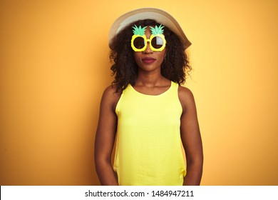 African american woman wearing funny pineapple sunglasses over isolated yellow background with serious expression on face. Simple and natural looking at the camera.