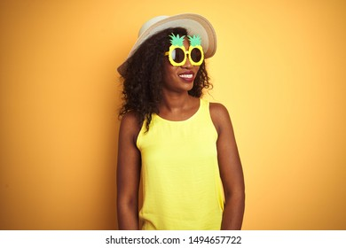 African american woman wearing funny pineapple sunglasses over isolated yellow background looking away to side with smile on face, natural expression. Laughing confident.