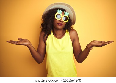 African american woman wearing funny pineapple sunglasses over isolated yellow background clueless and confused expression with arms and hands raised. Doubt concept.