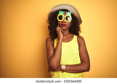 African american woman wearing funny pineapple sunglasses over isolated yellow background with hand on chin thinking about question, pensive expression. Smiling with thoughtful face. Doubt concept.