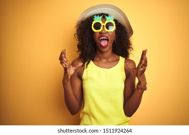 African american woman wearing funny pineapple sunglasses over isolated yellow background crazy and mad shouting and yelling with aggressive expression and arms raised. Frustration concept.