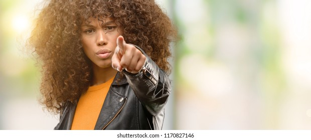 African american woman wearing a leather jacket pointing with finger to the camera and to you, hand sign, positive and confident gesture from the front