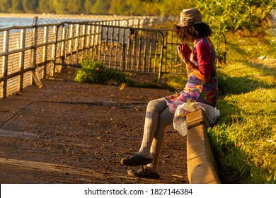 An African American woman wearing long gray socks and vibrant colored cotton dress is sitting crosslegged on a barrier wall by side walk playing with her hair and looking at Potomac river at sunset.