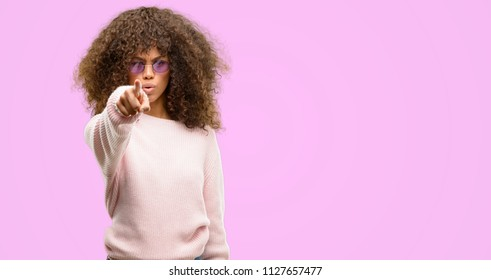 African american woman wearing a pink sweater pointing with finger to the camera and to you, hand sign, positive and confident gesture from the front