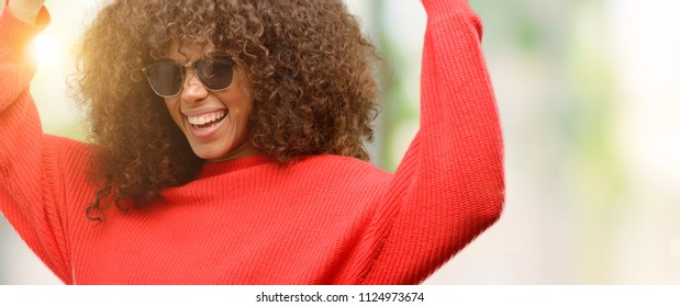 African american woman wearing sunglasses happy and excited celebrating victory expressing big success, power, energy and positive emotions. Celebrates new job joyful