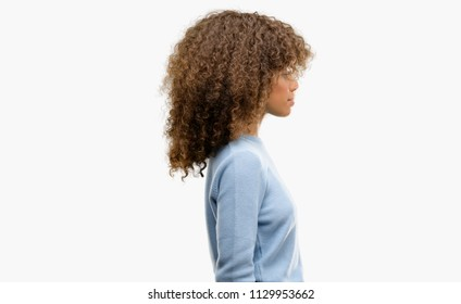 African american woman wearing a sweater looking to side, relax profile pose with natural face with confident smile.
