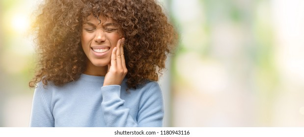 African american woman wearing a sweater touching mouth with hand with painful expression because of toothache or dental illness on teeth. Dentist concept.