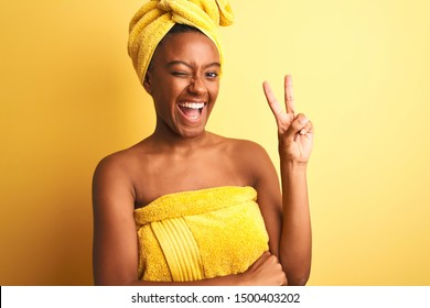 African american woman wearing towel after shower standing over isolated yellow background smiling with happy face winking at the camera doing victory sign. Number two.