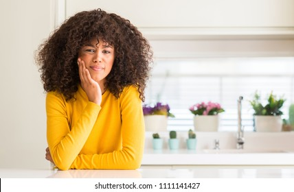 African american woman wearing yellow sweater at kitchen touching mouth with hand with painful expression because of toothache or dental illness on teeth. Dentist concept.