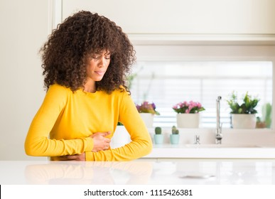 African american woman wearing yellow sweater at kitchen with hand on stomach because nausea, painful disease feeling unwell. Ache concept.