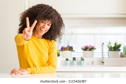 African american woman wearing yellow sweater at kitchen smiling looking to the camera showing fingers doing victory sign. Number two.