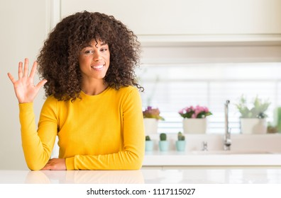 African american woman wearing yellow sweater at kitchen showing and pointing up with fingers number five while smiling confident and happy.