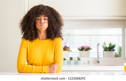 African american woman wearing yellow sweater at kitchen puffing cheeks with funny face. Mouth inflated with air, crazy expression.