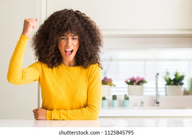 African american woman wearing yellow sweater at kitchen angry and mad raising fist frustrated and furious while shouting with anger. Rage and aggressive concept.