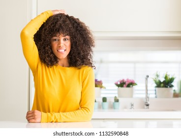 African american woman wearing yellow sweater at kitchen confuse and wonder about question. Uncertain with doubt, thinking with hand on head. Pensive concept.
