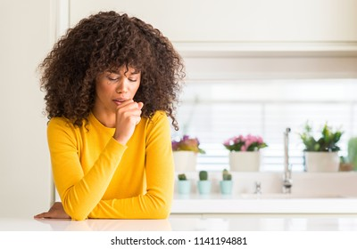 African american woman wearing yellow sweater at kitchen feeling unwell and coughing as symptom for cold or bronchitis. Healthcare concept.