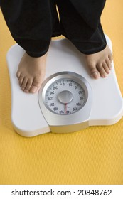 African American Woman weighing herself on a bathroom scale