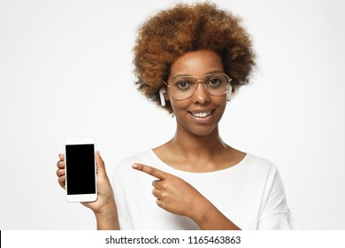 African american woman in white t shirt isolated on gray background, presenting smart phone and pointing with finger at blank black screen with copyspace for ads