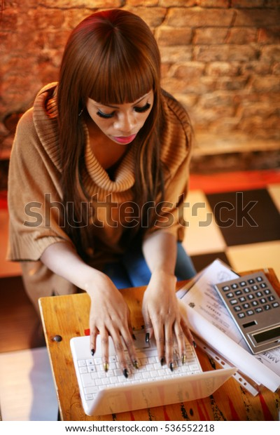 African American woman working on laptop at home.