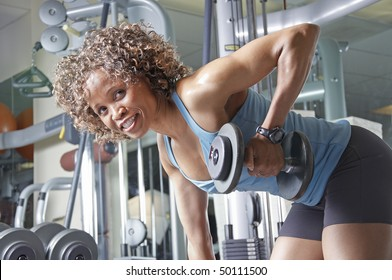 An African American woman working out in the gym with weights