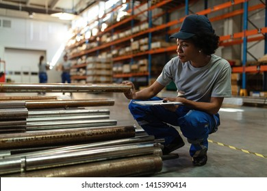 African American woman working in a warehouse and checking quality of manufactured metal products before the distribution.