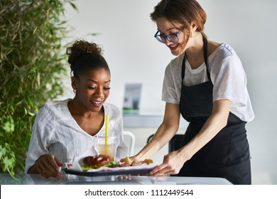 african american women being served tray of healthy vegan food at restaurant