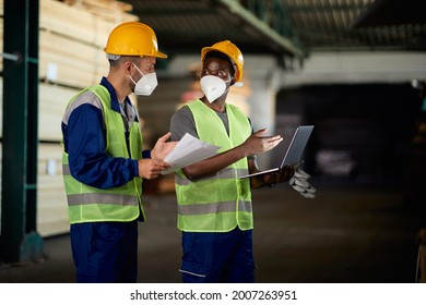African American worker and his colleague using laptop and communicating while working at lumberyard warehouse during COVID-19 pandemic.