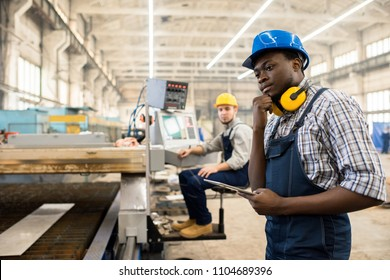 African American worker wearing overall and hardhat operating machine with help of digital tablet, interior of spacious production department of modern plant on background