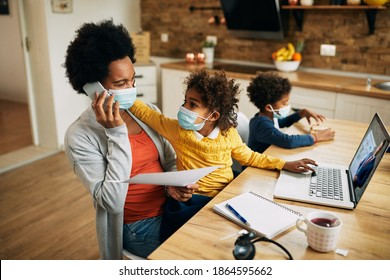 African American working mother talking on the phone while daughter is reminding her that she has online meeting over laptop at home.They are wearing protective face masks due to coronavirus pandemic.