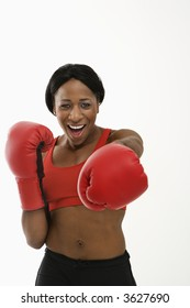 African American young adult woman wearing boxing gloves throwing playful punch at viewer.