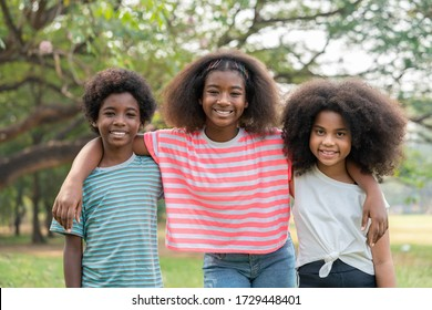 African American young boy and girl smiling and hugging look at camera in the park