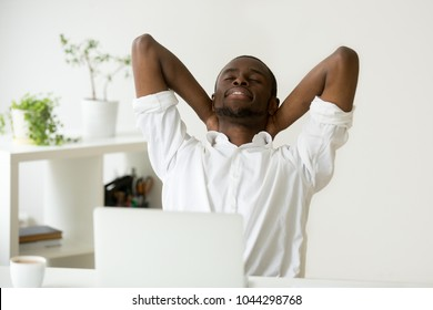 African american young businessman relaxing at workplace with laptop, relaxed calm black employee feels happy at work breathing fresh air, smiling man enjoys break stretching in office, peace of mind