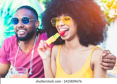African American young couple eating fruit and drinking cocktails - summer party with friends and healthy food concept