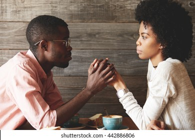 African American young couple sitting at a cafe table: black man in glasses holding her beautiful wife's hands, begging her to forgive him, apologizing for an affair, looking with guilty expression