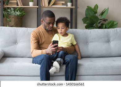 African American young dad and biracial preschooler child spend time together watch football on smartphone, surprised black father and little son sit on couch enjoy cartoon or video on cellphone